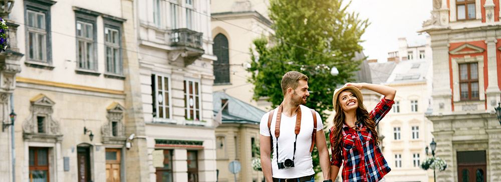 Tourist Couple Walking On Street Together. Happy Young Man And Smiling Woman Walking Around Old Town Streets, Looking At Architecture. Travel Concept